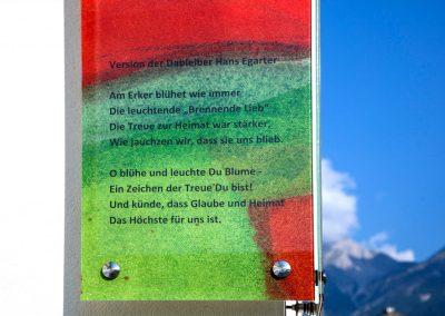 Text auf Eckverglasung der Südtirolersiedlung in Absam mit Blick in die Berge © Gestaltung Hilde Chistè © Aufnahme Dorfstterer
